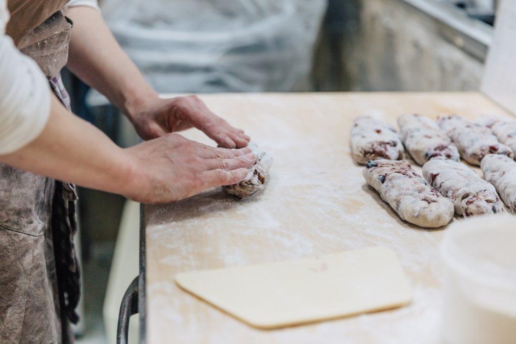工房でパンをこねるオーナーシェフ北村千里さんの手元アップ